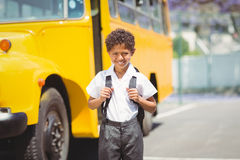 Cute pupil smiling at camera by the school bus. Outside the elementary school Stock Photography