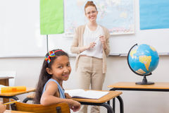 Cute pupil and teacher in classroom with globe. At the elementary school Stock Photos