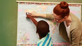 Cute pupil and teacher pointing to map. At the elementary school stock video