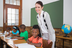 Cute pupil and teacher smiling at camera in classroom Royalty Free Stock Image