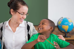 Cute pupil and teacher smiling at each other in classroom Royalty Free Stock Image