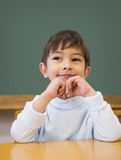 Cute pupil thinking at desk in classroom Stock Photography
