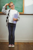Cute pupil thinking and holding books in a classroom Royalty Free Stock Image