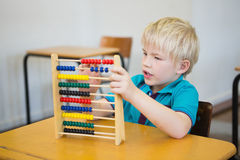 Cute pupil using abacus in classroom. At the elementary school royalty free stock photo