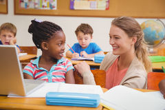 Cute pupil using computer with teacher Royalty Free Stock Photo
