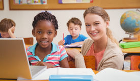 Cute pupil using computer with teacher Stock Photography