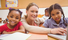 Cute pupil using computer with teacher Stock Images