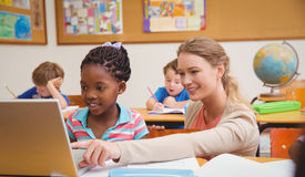 Cute pupil using computer with teacher. At the elementary school Royalty Free Stock Images