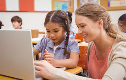 Cute pupil using computer with teacher. At the elementary school Royalty Free Stock Photography