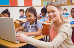 Cute pupil using computer with teacher. At the elementary school Stock Photography