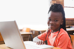 Cute pupil using laptop in classroom Royalty Free Stock Photo