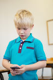 Cute pupil using smartphone in classroom Royalty Free Stock Images