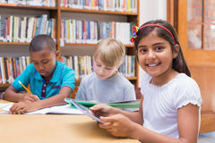 Cute pupil using tablet computer in library Royalty Free Stock Photography