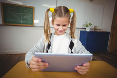 Cute pupil using tablet at her desk in a classroom Royalty Free Stock Photo
