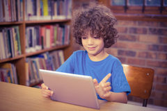 Cute pupil using tablet in the library. In school Royalty Free Stock Image