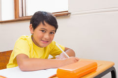 Cute pupil writing at desk in classroom Stock Photography