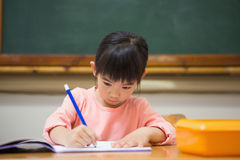 Cute pupil writing at desk in classroom royalty free stock photo