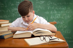 Cute pupil writing at desk Royalty Free Stock Images