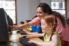 Cute pupils in computer class with teacher Royalty Free Stock Photos