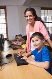 Cute pupils in computer class with teacher Royalty Free Stock Photo