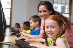 Cute pupils in computer class with teacher Stock Photos