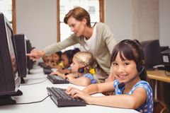 Cute pupils in computer class with teacher. At the elementary school Stock Photos