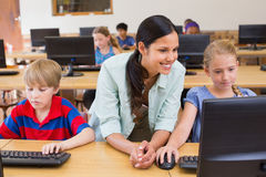 Cute pupils in computer class with teacher Royalty Free Stock Image