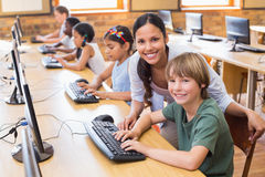 Cute pupils in computer class with teacher. At the elementary school Stock Photography