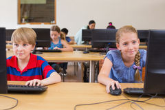 Cute pupils in computer class with teacher Stock Photo