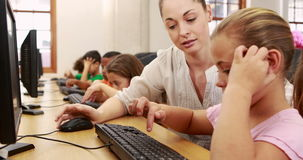Cute pupils in computer class with teacher. At the elementary school stock video footage
