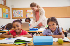 Cute pupils drawing at desk in classroom Stock Image