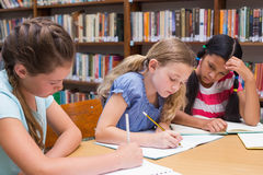 Cute pupils drawing in library Royalty Free Stock Images
