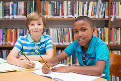 Cute pupils drawing in library Stock Images