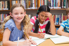 Cute pupils drawing in library Royalty Free Stock Photos