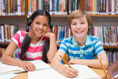 Cute pupils drawing in library Royalty Free Stock Photography