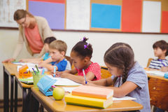 Cute pupils drawing at their desks Royalty Free Stock Image