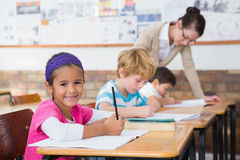 Cute pupils drawing at their desks one smiling at camera Royalty Free Stock Photography