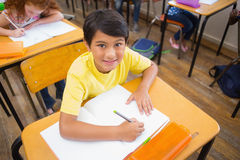 Cute pupils drawing at their desks one smiling at camera Royalty Free Stock Images
