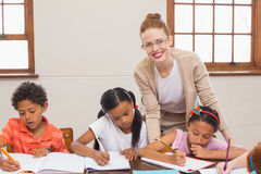 Cute pupils getting help from teacher in classroom Royalty Free Stock Photos