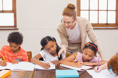 Cute pupils getting help from teacher in classroom Stock Photos