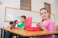 Cute pupils having their lunch in classroom. At the elementary school stock photo