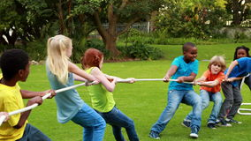 Cute pupils having a tug of war. Outside the elementary school stock video footage