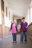 Cute pupils holding hands in corridor Stock Photos