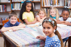 Cute pupils looking at camera in library Royalty Free Stock Image