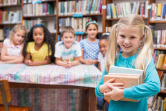 Cute pupils looking at camera in library Stock Photos