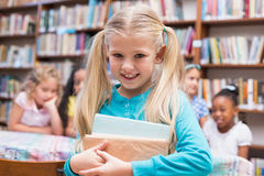 Cute pupils looking at camera in library Royalty Free Stock Images