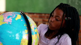Cute pupils looking at the globe in classroom. In elementary school stock video footage