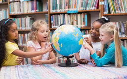 Cute pupils looking at globe in library Royalty Free Stock Photos