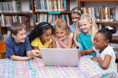 Cute pupils looking at laptop in library Royalty Free Stock Image