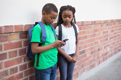 Cute pupils looking at smartphone in corridor Royalty Free Stock Photography